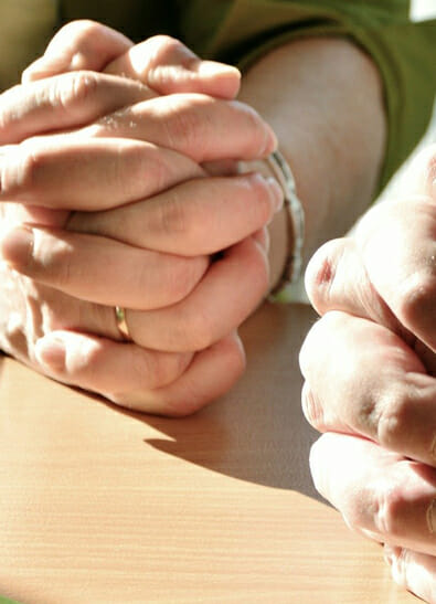 Close-up of two hands clasped in prayer